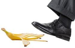Voet in de linker zwarte schoenmisstappen op een banaanschil Royalty-vrije Stock Afbeelding