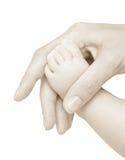 Voet van het kind in een hand van mum. Stock Afbeeldingen