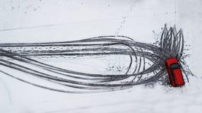 Voetafdrukken in de sneeuw van de auto Rode auto luchtfotografie stock fotografie