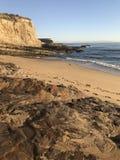 Voetafdrukken die de kustlijn van Californië met oceaan, klip, strand, rotsen en duidelijke blauwe hemel kruisen royalty-vrije stock fotografie