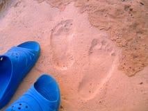 Voetafdrukken en schoenen op het zand royalty-vrije stock afbeeldingen