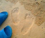 Voetafdrukken en schoenen op het zand Stock Fotografie