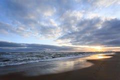 Voetafdrukken in het zand door het overzees stock afbeeldingen