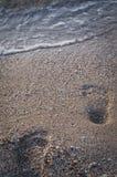 Voetafdrukken in het zand op het overzeese strand Stock Foto's