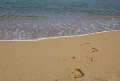 Voetafdrukken in het zand op het overzeese strand stock afbeelding