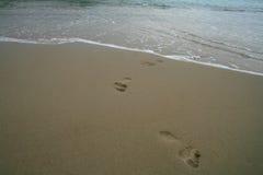 Voetafdrukken op een zandig strand stock foto