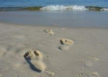 Voetafdrukken op het strandzand Stock Afbeeldingen