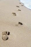 Voetafdrukken op overzees strandzand met golfschuim Stock Afbeeldingen