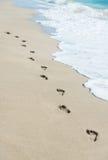 Voetafdrukken op overzees strandzand met golfschuim Stock Foto's