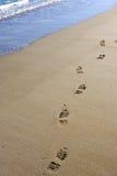 Voetafdrukken op verlaten zandig strand Stock Afbeeldingen