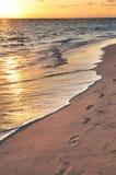 Voetafdrukken op zandig strand bij zonsopgang Stock Fotografie