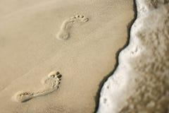 Voetafdrukken in zand naast golf. royalty-vrije stock foto