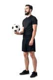 Voetbal of de holdingsbal van de voetbal futsal speler in één hand die omhoog eruit zien royalty-vrije stock foto
