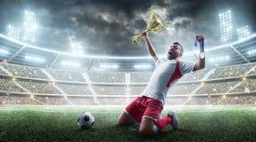 Voetbal De professionele voetballer viert het winnen van voetbalgelijke het open stadion De voetballer houdt een kop en a royalty-vrije stock fotografie