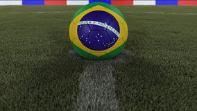 Voetbal/voetbal defocused de klassieke bal in het centrum van het gebiedsgras met het schilderen van de vlag van Brazilië met die stock fotografie