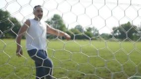Voetbal die de rug van het net in langzame motie raken stock footage
