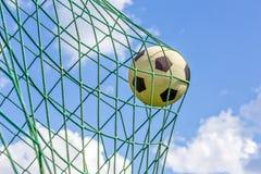 Voetbal die in netto doel wordt geschoten stock afbeelding