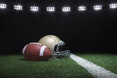Voetbal en helm op grasgebied onder stadionlichten bij nacht Royalty-vrije Stock Foto