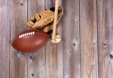Voetbal en honkbalmateriaal op rustieke houten raad Royalty-vrije Stock Foto