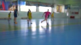 Voetbal futsal opleiding voor kinderen Binnenvoetbal jonge speler met een voetbalbal in een sporthal stock videobeelden