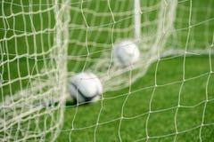 Voetbal netto met uit-nadrukballen op achtergrond stock foto