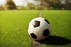 Voetbal op groen gras stock foto