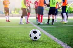 Voetbal op groen kunstmatig gras met onscherpe voetballers status stock afbeelding