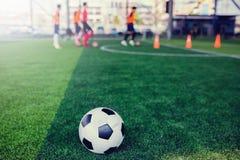 Voetbal op groen kunstmatig gras met onscherpe voetbalteam opleiding stock foto