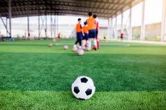 Voetbal op groen kunstmatig gras met onscherpe voetbalteam opleiding royalty-vrije stock fotografie