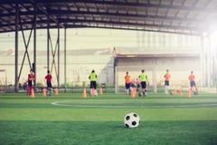 Voetbal op groen kunstmatig gras met onscherpe voetbalteam opleiding stock foto's