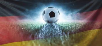 Voetbal op stadiongazon met de vlag van Duitsland stock fotografie