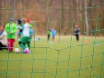 Voetbal opleiding Gekruiste het voetbalvoetbal van voetbalnetten in doel netto met gras stock foto's