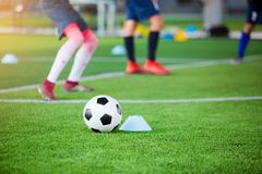 Voetbal tussen tellerskegels op groen kunstmatig gras met onscherpe voetbalteam opleiding stock afbeelding