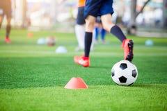 Voetbal tussen tellerskegels op groen kunstmatig gras met onscherpe voetbalteam opleiding royalty-vrije stock foto's