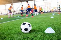 Voetbal tussen tellerskegels op groen kunstmatig gras met onscherpe voetbalteam opleiding royalty-vrije stock afbeelding