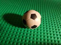 voetbalbal als centrum van alles, op groene 3d textuur Stock Fotografie