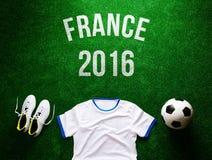 Voetbalbal, cleats en witte t-shirt tegen kunstmatig gras Royalty-vrije Stock Fotografie
