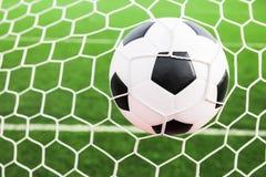 Voetbalbal in het netto doel royalty-vrije stock afbeeldingen