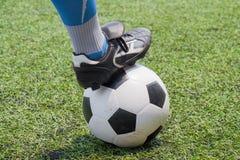 Voetbalbal met zijn voeten stock foto