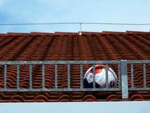 Voetbalbal op dak wordt geplakt dat stock foto