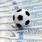 Voetbalbal op dollarbankbiljetten, close-up Het wedden op sportconcept Vierkante omlijsting Het spel van de voetbalcorruptie Royalty-vrije Stock Afbeeldingen