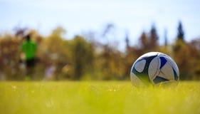 Voetbalbal op gebied op de rechterkant klaar om worden geschopt Vage spelers en aardachtergrond stock fotografie