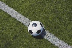 Voetbalbal op groen gras over de witte lijn royalty-vrije stock foto