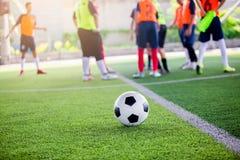 Voetbalbal op groen kunstmatig gras met onscherpe voetballers stock foto's