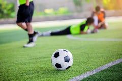 Voetbalbal op groen kunstmatig gras met onscherpe voetballers status stock afbeelding