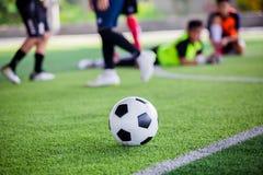 Voetbalbal op groen kunstmatig gras met onscherpe voetballers status royalty-vrije stock afbeeldingen