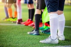 Voetbalbal op groen kunstmatig gras met onscherpe voetballers status stock afbeeldingen