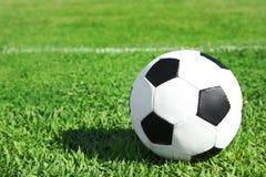 Voetbalbal op het verse groene gras van het voetbalgebied stock fotografie