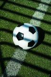 Voetbalbal zwart-wit op kunstmatige grondgrond met schaduwenstrepen, op de lijn stock fotografie