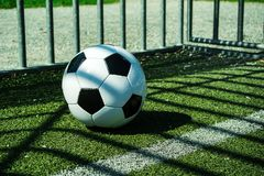 Voetbalbal zwart-wit op kunstmatige grondgrond met schaduwenstrepen, over de lijn royalty-vrije stock foto